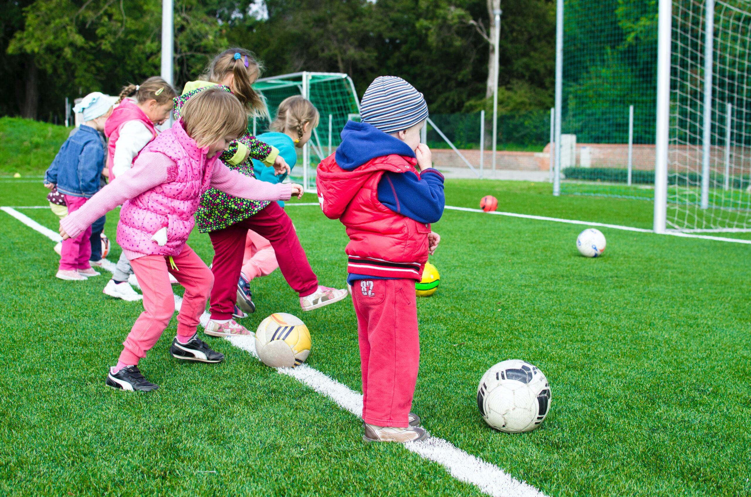 Nens jugant a la pilota en un camp de futbol